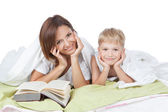 Happy family - mother and son lying on the white bed — Stock Photo