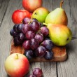 Harvested grapes, apples, ripe pears and plums — Stock Photo