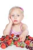 Little girl eating red berries on white — Stock Photo