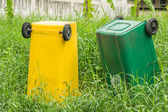 Bin on overgrown weed area — Stock Photo