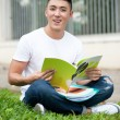 Royalty-Free Stock Photo: Asian handsome young student man reading book in the park