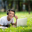 Young handsome asian student using laptop in the park — Stock Photo