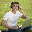 Young handsome Asian student with laptop and headset out door — Stok fotoğraf