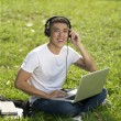 Young handsome Asian student with laptop and headset out door — Stock Photo #21584829