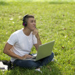 Young handsome Asian student with laptop and headset out door — Stock Photo
