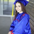 Portrait of a beautiful young asian woman in graduation cap and gown standing outside on campus — Stock Photo #21683245