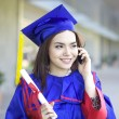 Portrait of a beautiful young asian woman in graduation cap and talking on the mobile phone — Stock Photo