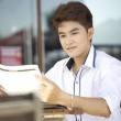 A asian student with newspaper outdoor — Stock Photo #21681043