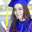 Portrait of a beautiful young asian woman in graduation cap and gown standing outside on campus — Stock Photo #21683681