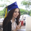 Happy businesswoman sitting at her workplace and smile with graduation cap - Stock Photo