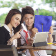 Asian couple using laptop outdoor — Stock Photo
