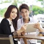 Asian couple using laptop outdoor — Stock Photo