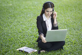 Beautiful Asian woman using computer in the outdoor — Stock Photo