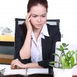 Headache and Stress at work. Young professional woman stressed and tired with headache sitting at office desk, holding medicine pills — Stockfoto