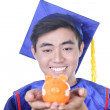 Young Asian graduation student guy with piggy bank - isolated on white — Stock Photo