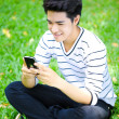 Young handsome Asian student with phone in outdoor — Стоковая фотография