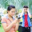 Young Asian couple with phone in outdoor — Foto de Stock