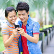 Young Asian couple with phone in outdoor — Stock Photo