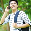 Young handsome Asian student with phone in outdoor — Foto Stock