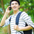 Young handsome Asian student with phone in outdoor — ストック写真