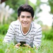Young handsome Asian student with phone in outdoor — Zdjęcie stockowe
