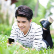 Young handsome Asian student with phone in outdoor — Photo