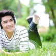 Young handsome Asian student with headset out door — Stock Photo