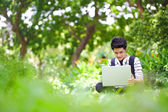 Young handsome Asian student with computer in outdoor — Stok fotoğraf