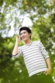 年轻英俊的亚洲学生用手机在户外 — 图库照片