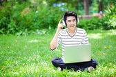 Young handsome Asian student with computer in outdoor — Stock Photo
