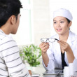 Asian young female doctor checking patient — Stock Photo