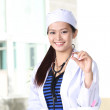 Doctor woman showing pill. Young female medical professional. Multiracial Asian Caucasian model — Stock Photo