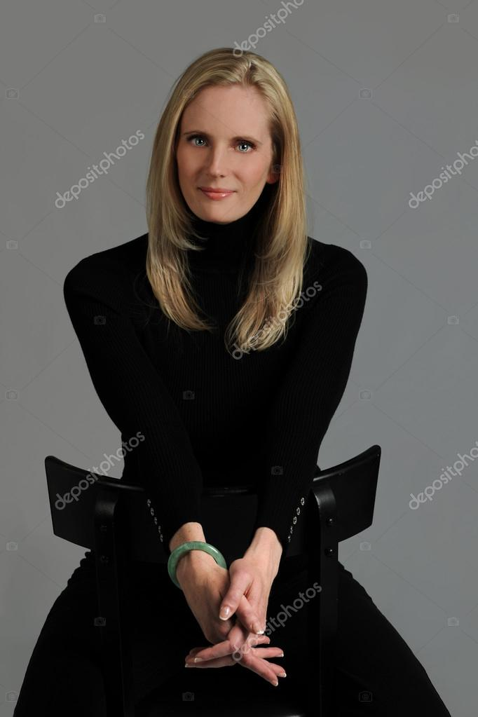 Portrait of young woman seated on chair over neutral background — Stock Photo #13325614