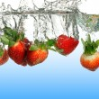 Strawberries Splashing into Water — Stock Photo #13390828