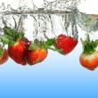 Strawberries Splashing into Water — Stock Photo #13390828