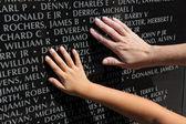 成人和儿童触摸名称在战争纪念馆的手 — 图库照片