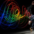 Stock Photo: Dancer with Waves of Light Over Black Background