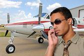 Ung man talar i en mobiltelefon på flygplats — Stockfoto