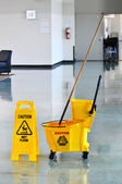 Mop and Bucket with Caution Sign — Stock Photo