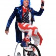 Clown Riding Unicycle with Training Wheels - Stock Photo