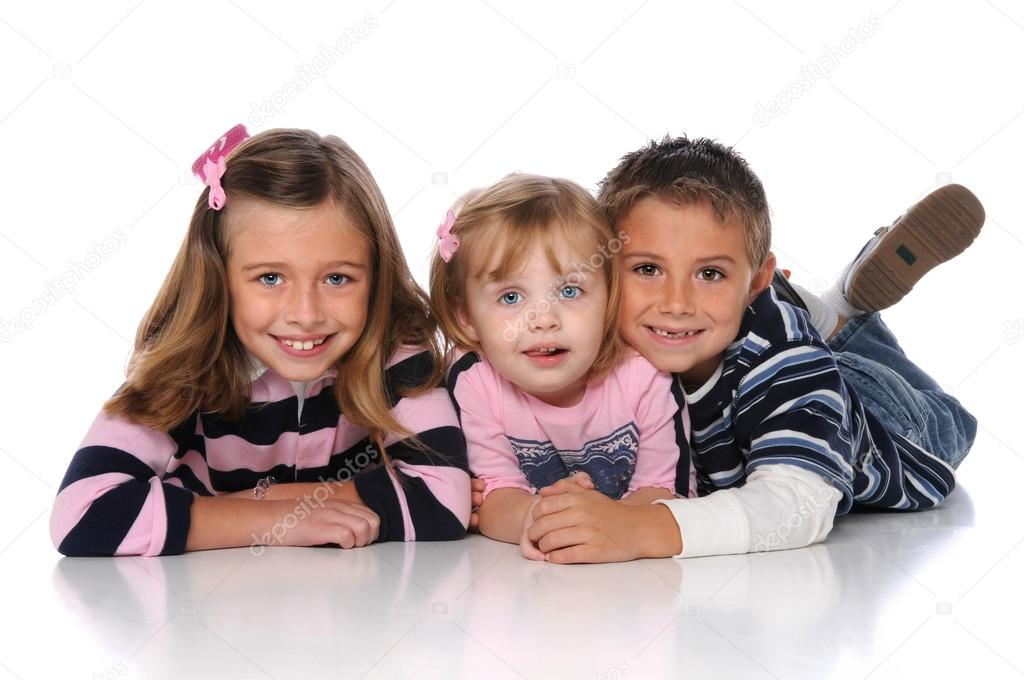 Children laying on the floor smiling over a white background  Stock Photo #15391465