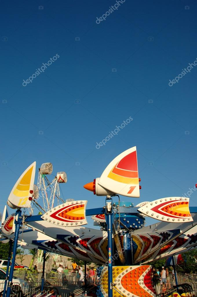 Carnival rides in a colorful display over a blue sky. — Stock Photo #16631905