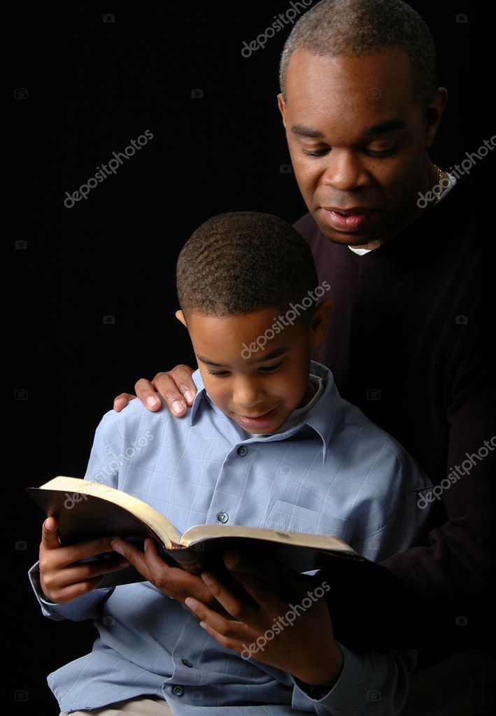 Father and son reading a Bible over a black background.  Stock Photo #16856009