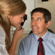 Eye Doctor Examining Hispanic Patient - Stock Photo