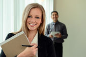 Businesswoman In Office with Coworker in Background — Stock Photo