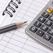 Gray pencil, calculator on notebook — Stock Photo