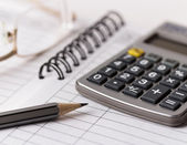 Gray pencil, glasses and calculator on notebook — Stock Photo