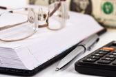 Nota de agenda, gafas, calculadora, lápiz y dólar — Foto de Stock