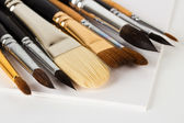 Artist brushes on sketchbook sheets — Stock Photo