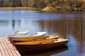 Pleasure boats attached to wooden pier on the pond in sunbeam — Stock Photo